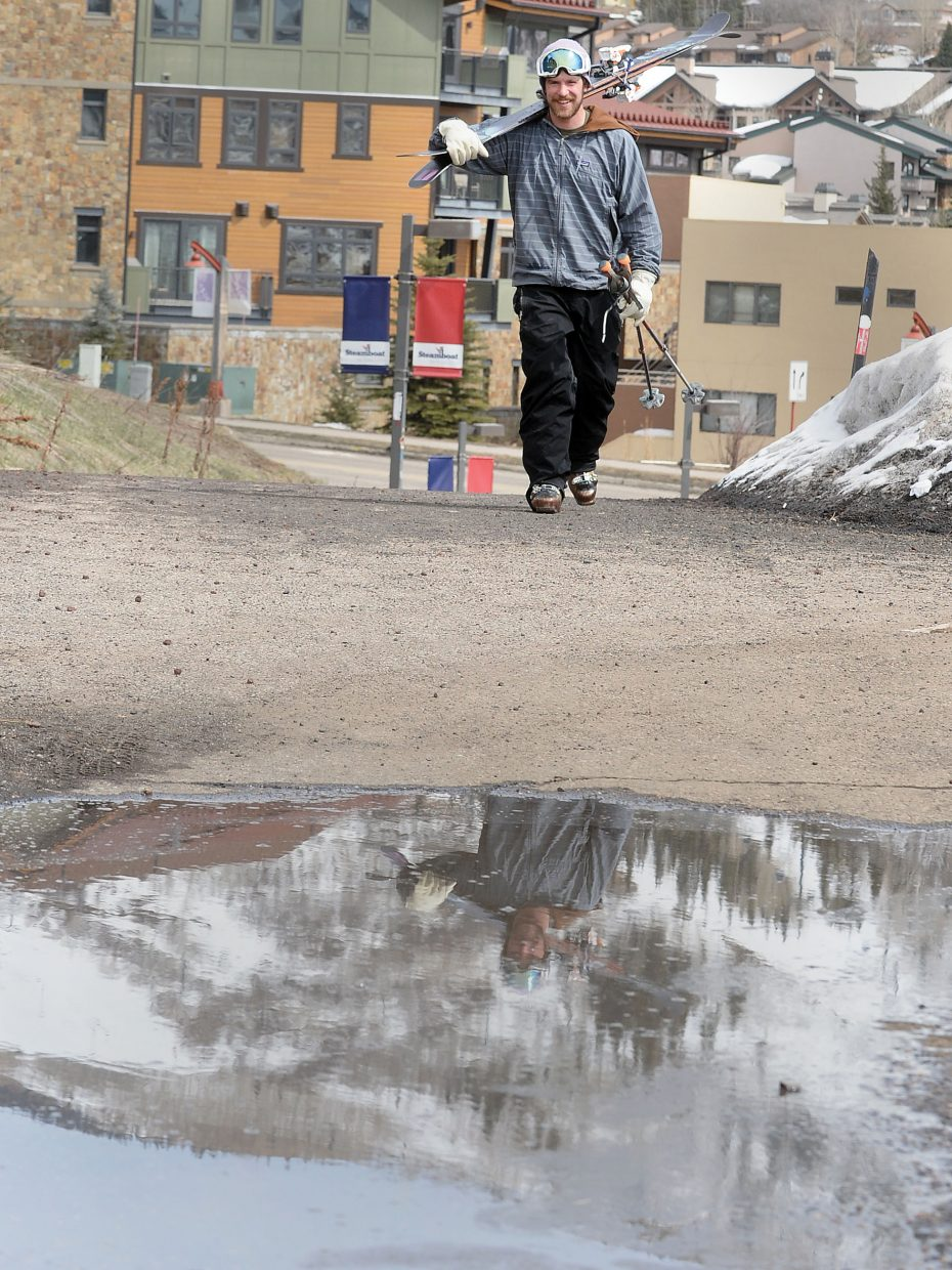Skier Kellen Johnson is reflected in a puddle Monday as he heads for home after a great day of spring skiing at Steamboat Ski Area.