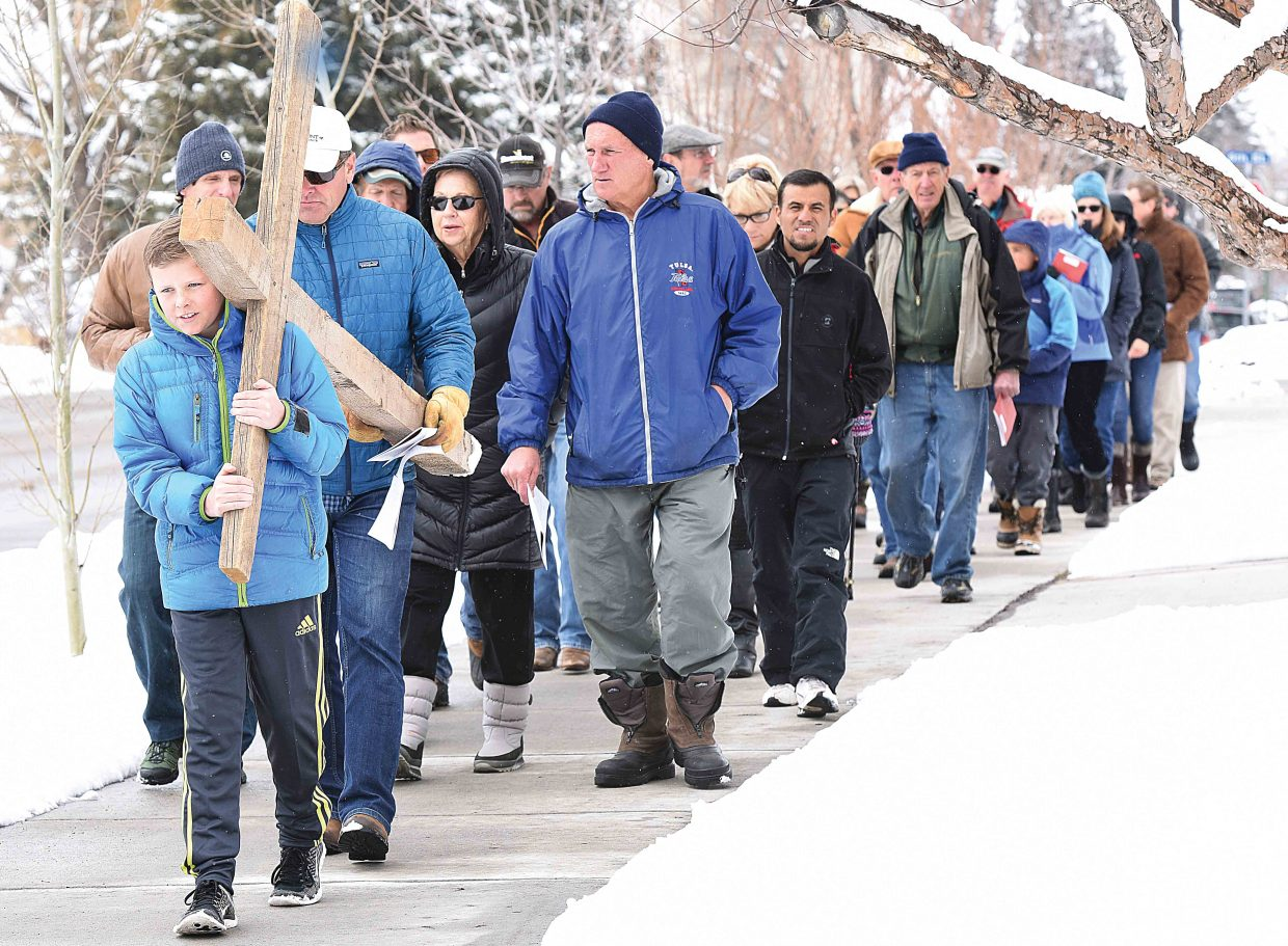 Steamboat Springs Jackson Metzler carries the cross down Oak Street Friday afternoon as part of the annual Stations of the Cross, or the way of the Cross, which is a symbolic pilgrimage highlighting the suffering of Christ as he made his way to Calvary.