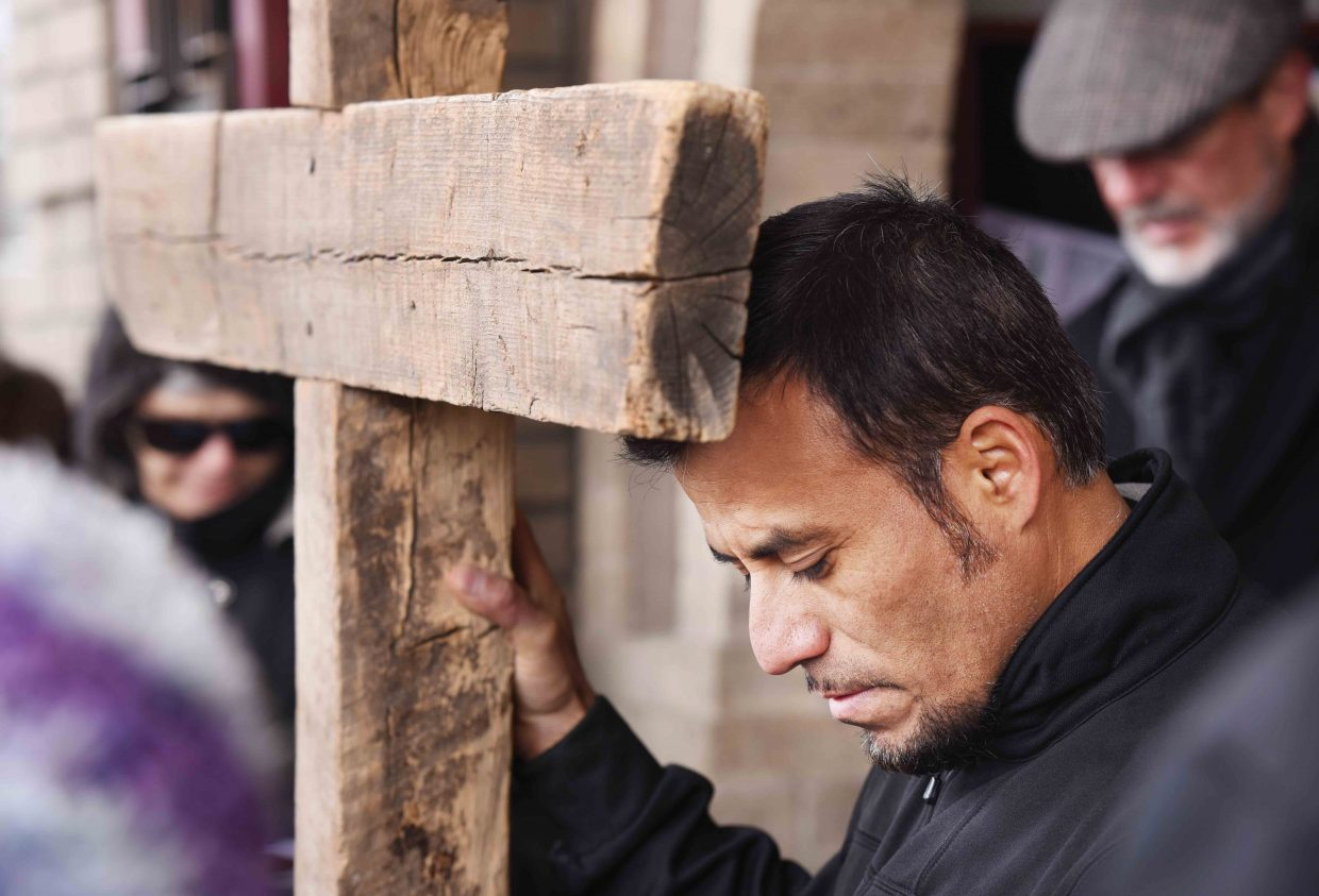 Alfredo Jimenez prays while holding the cross during this year's Stations of the Cross in downtown Steamboat Springs.