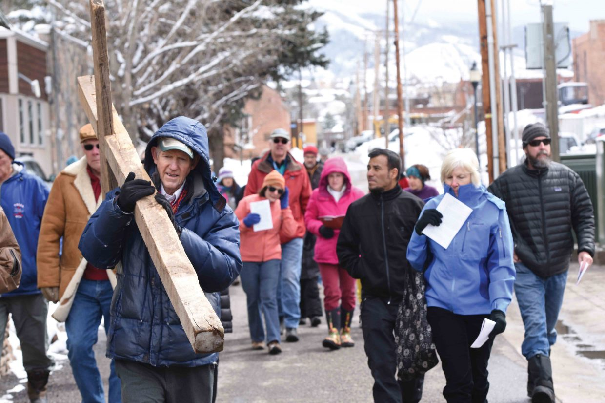 Longtime resident Bill Padgett carries the cross through downtown Steamboat Springs Friday afternoon as part of the annual Stations of the Cross. The group stopped at 14 different downtown locations for a few moments of prayer at each.