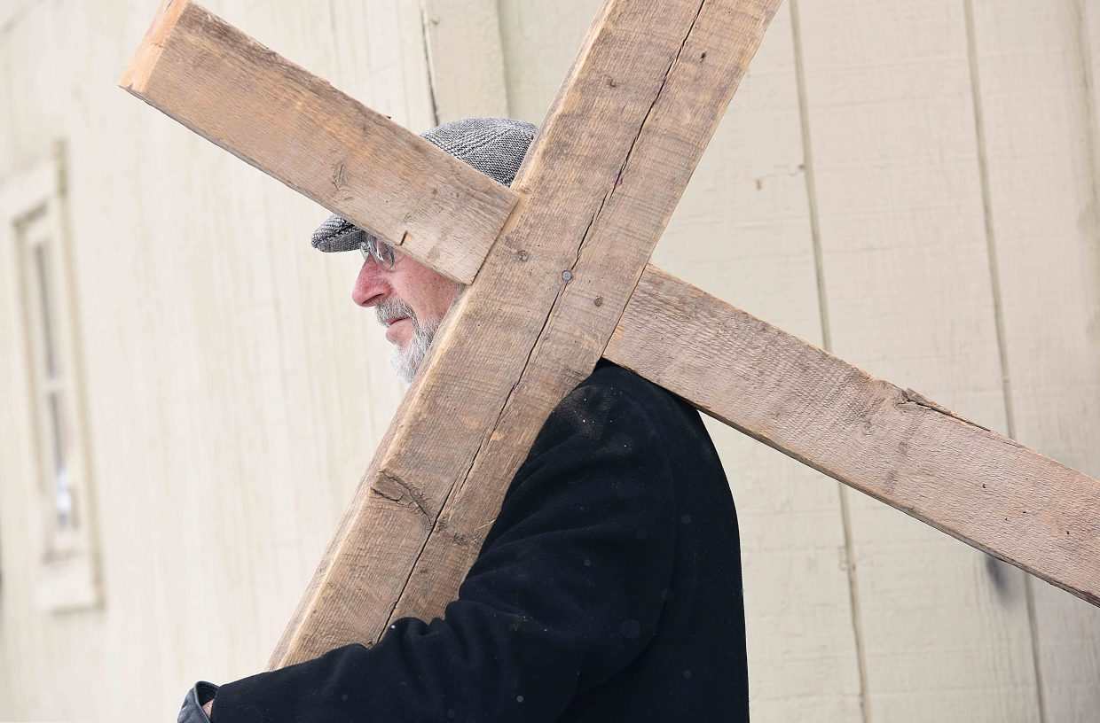 Rev. J. Scott Turner carries the cross through downtown Steamboat Springs Friday afternoon as part of the annual Stations of the Cross, a symbolic pilgrimage highlighting the suffering of Christ as he made his way to Calvary.