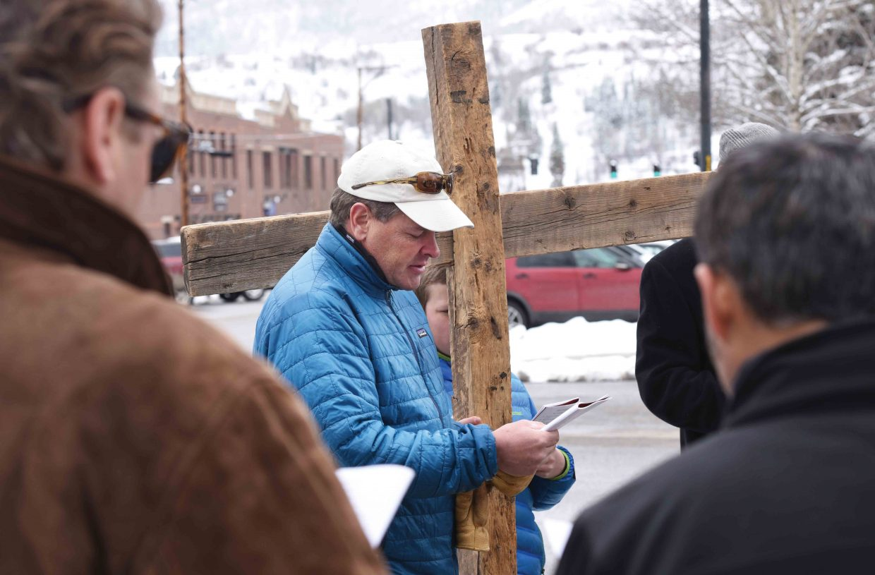 Nick Metzler prays while holding the cross during this year's Stations of the Cross in downtown Steamboat Springs. The annual remembrance is just one of many events leading up to Easter Sunday.