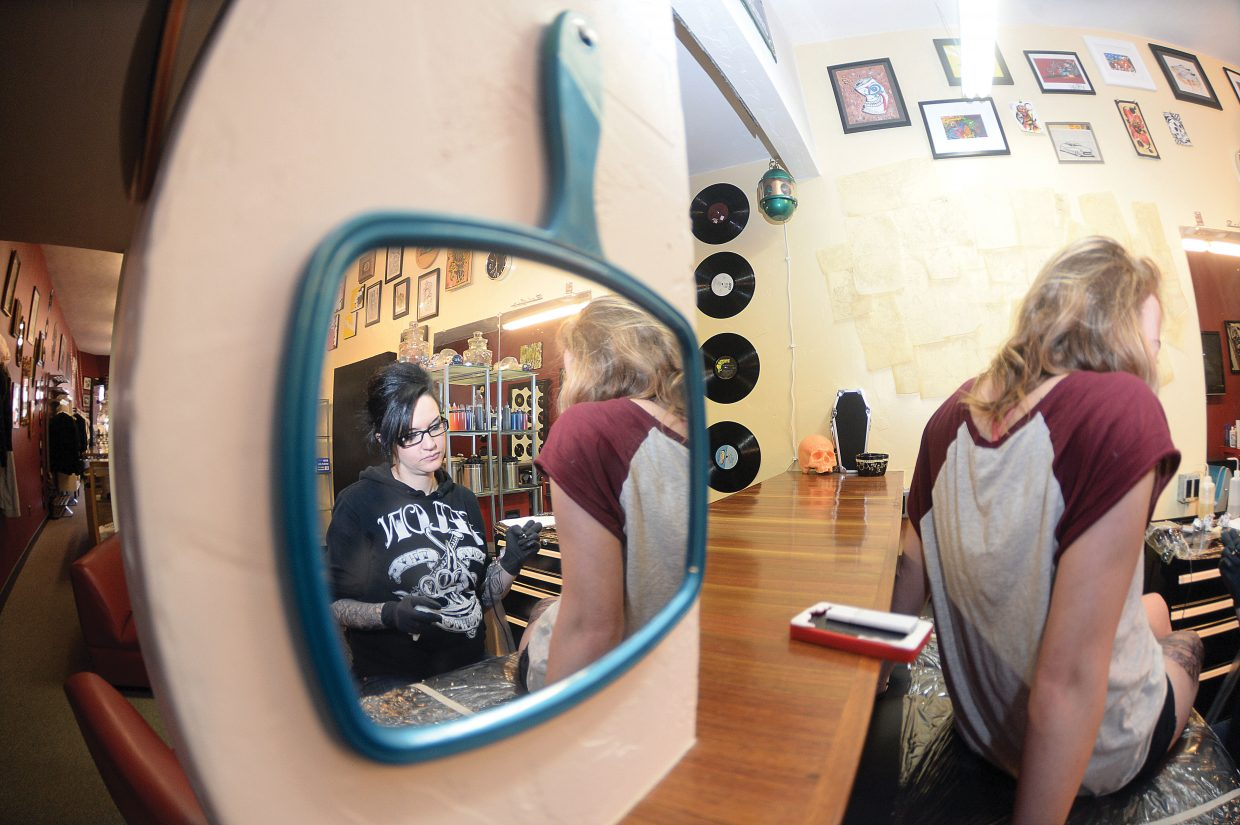 Local tattoo artist Melissa Freeman and client Ciera Barber are reflected in a mirror at Deluxe Tattoo in downtown Steamboat Springs. This photo and others in the series were taken by John F. Russell. The photo essay won first place in the 2014 Colorado Press Association's Better Newspaper Contest.