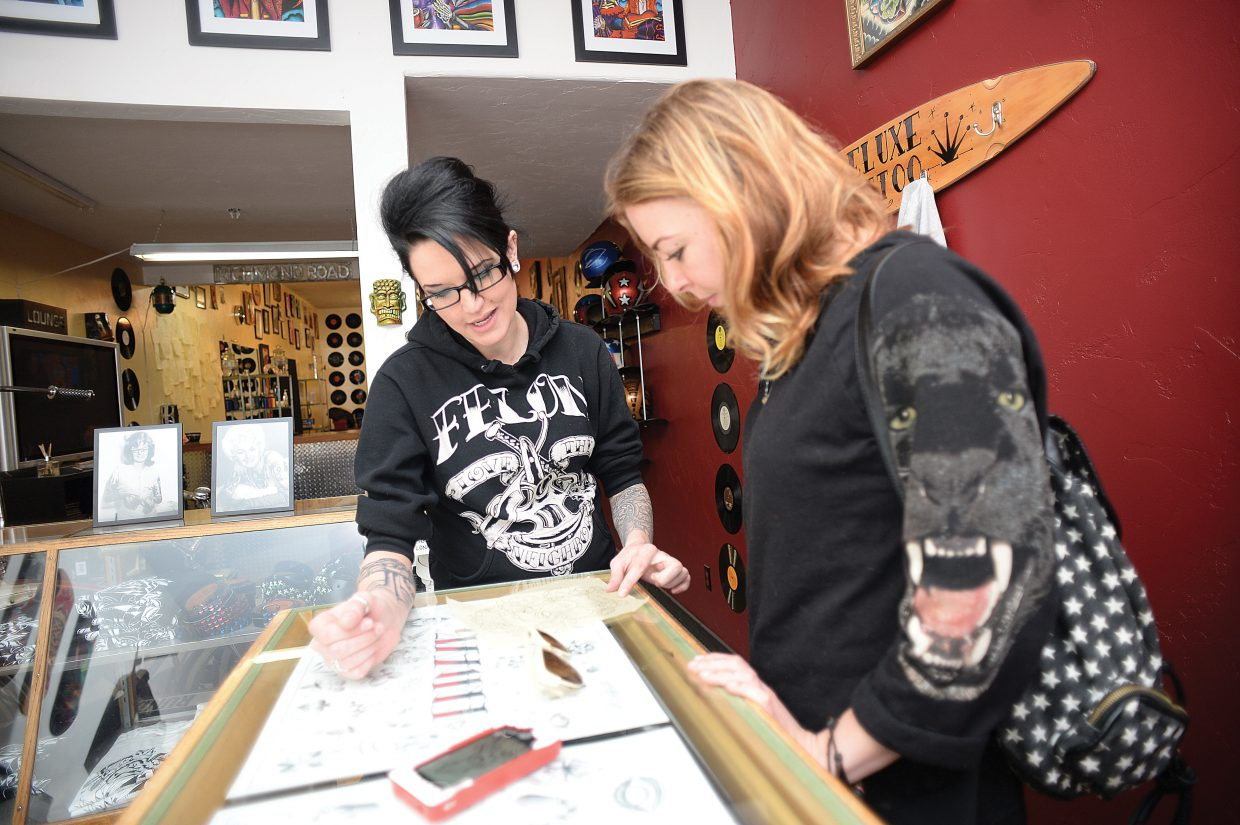 Tattoo artist Melissa Freeman goes over her drawings with client Ciera Barber before getting a tattoo.