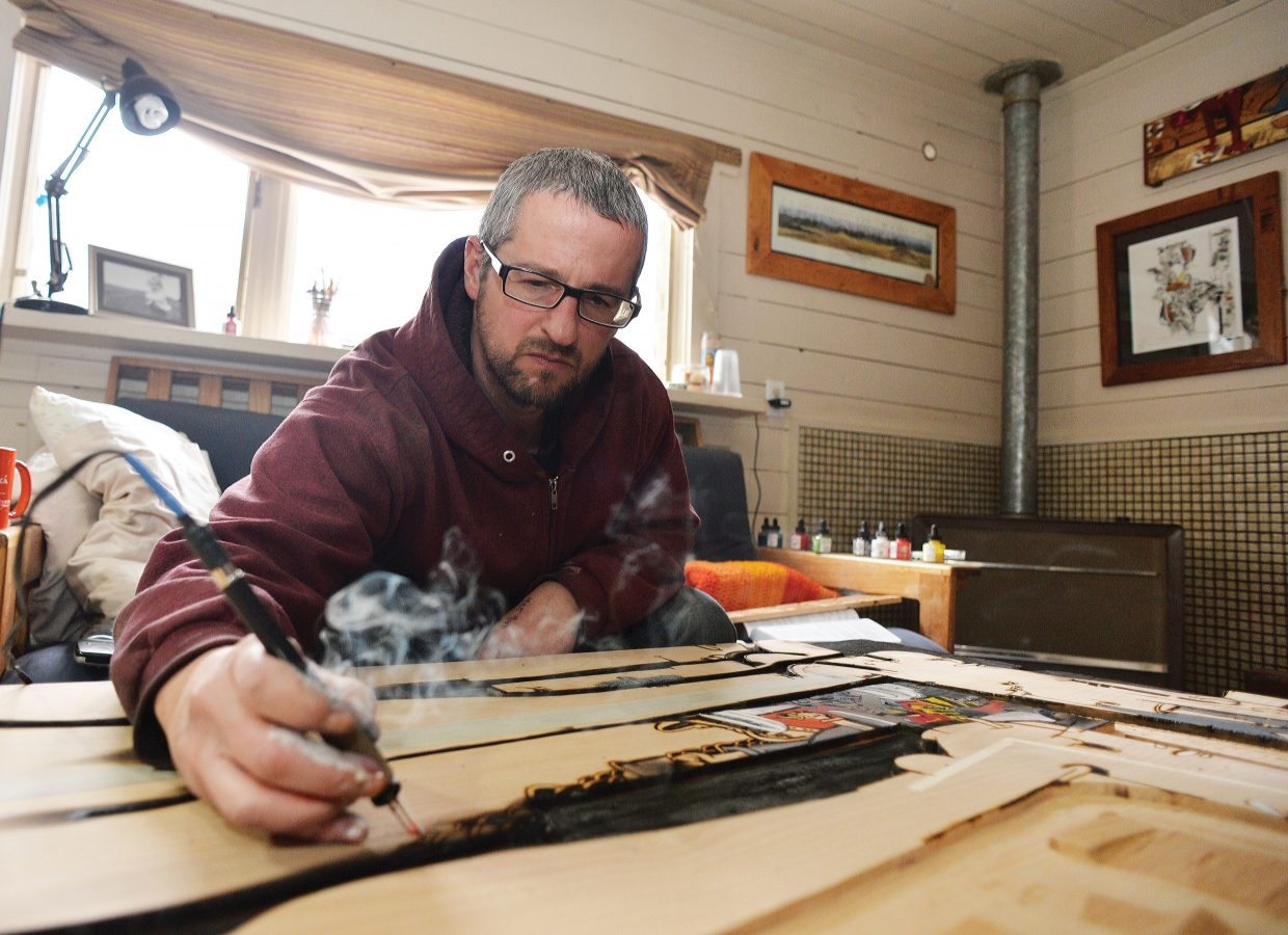 Local artist Brian Leach works on a piece in his downtown home. Leach, who is a carpenter by trade and makes furniture, has expanded his horizons into the world of art. He used a wood burner, paint and stains to create his unique works of art.
