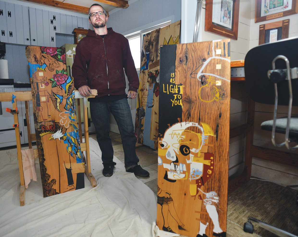 Local artist Brian Leach stands with his art in his downtown home. Leach, who is a carpenter by trade and makes furniture, has expanded his horizons into the world of art. He used a wood burner, paint and stains to create his unique works of art.