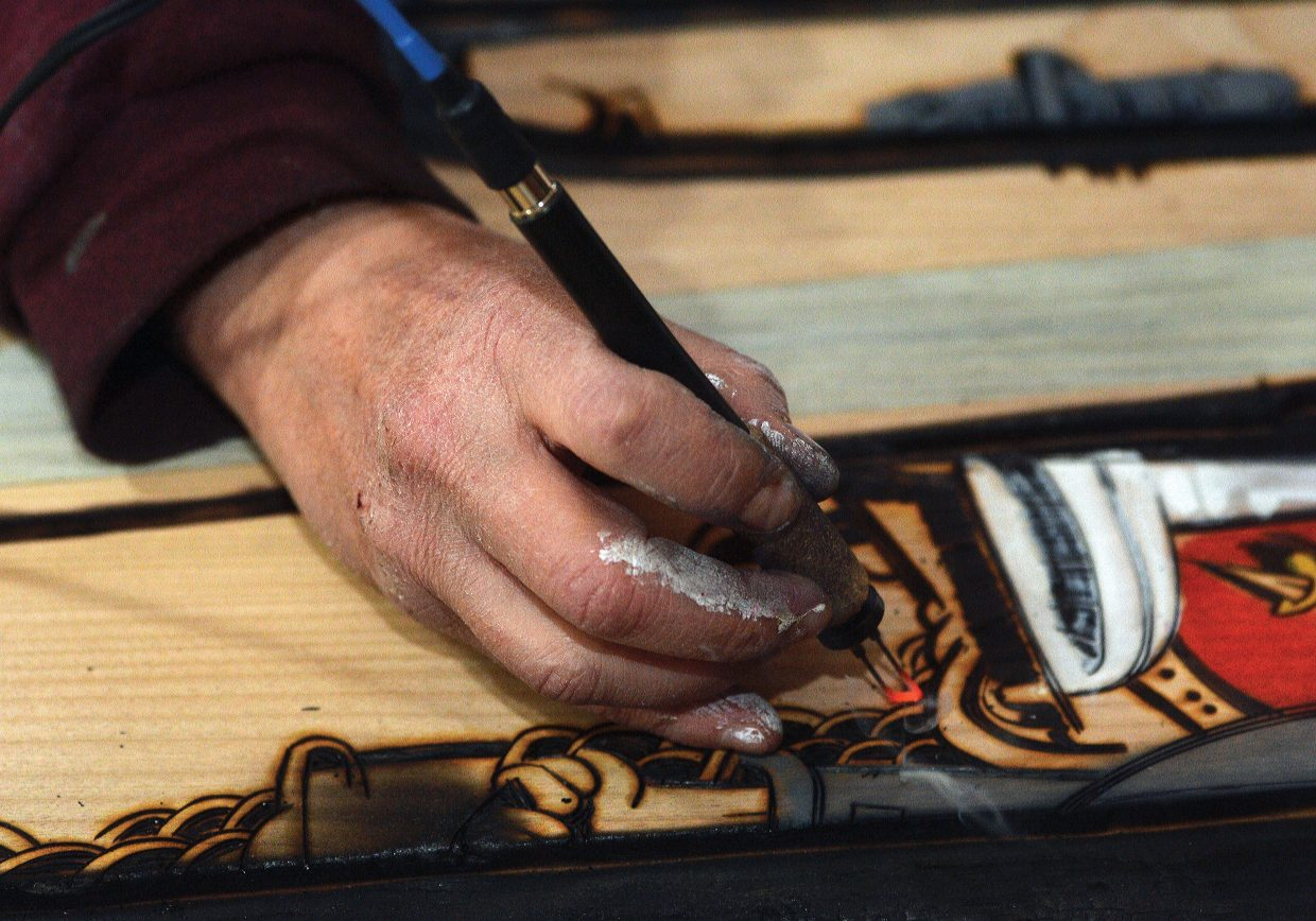 Local artist Brian Leach uses wood burning tools while working on a piece in his downtown home. Leach, who is a carpenter by trade and makes furniture, has expanded his horizons into the world of art. He used a wood burner, paint and stains to create his unique works of art.