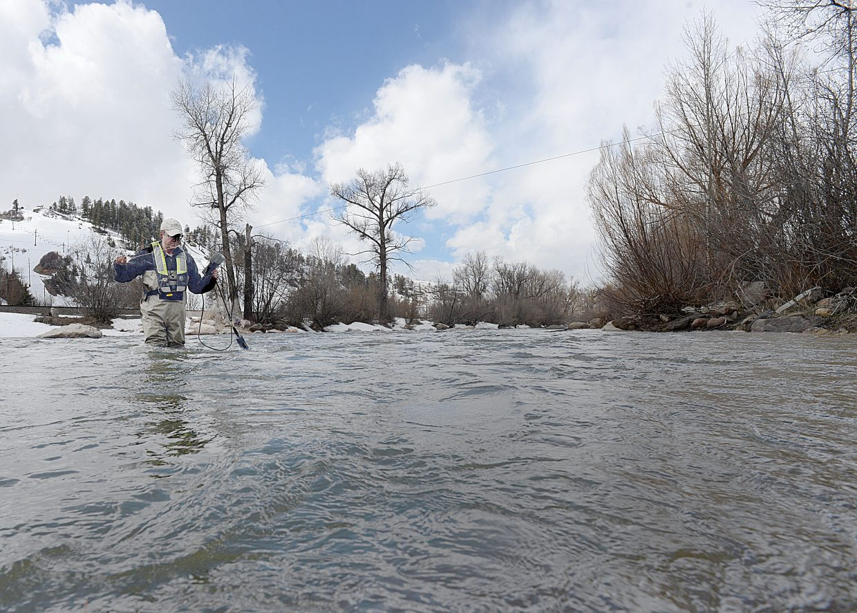 Terry Petrosky, who works for the U.S. Geological Survey, tests the water flowing down the Yampa River last week. The Colorado Basin River Forecast Center in Salt Lake City is signaling that a warming trend could kick off low-elevation runoff, causing the Yampa River in Steamboat Springs to begin to rise steeply.