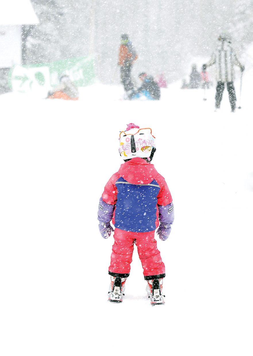 Snow falls from the sky Friday morning as 3-year-old McKenzie Maines heads for Why Not ski run with her family.