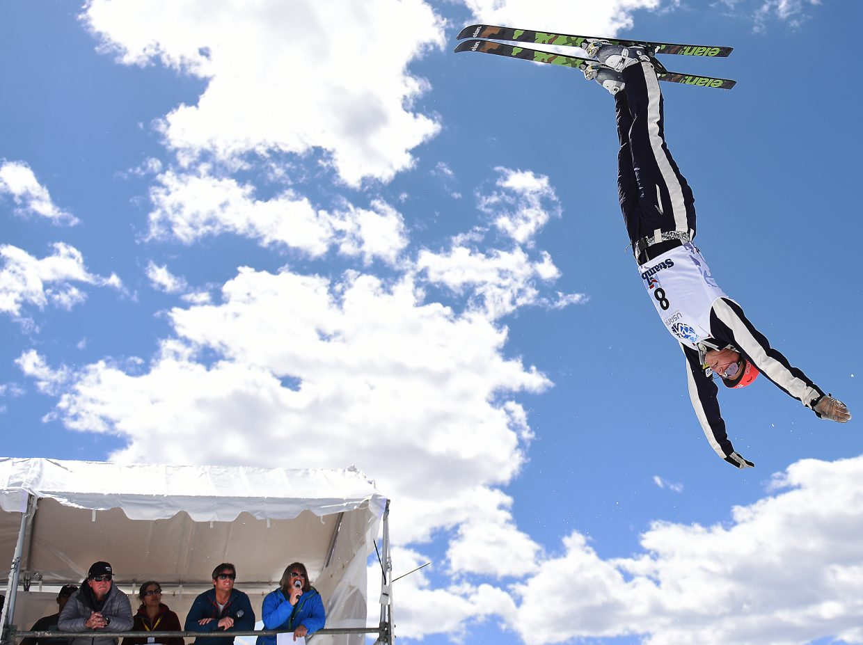 Tyra Izor flips above through the air as Bruce Perry, right, and Nelson Carmichael announce the action at the U.S. Freestyle Skiing Championships in Steamboat Springs.