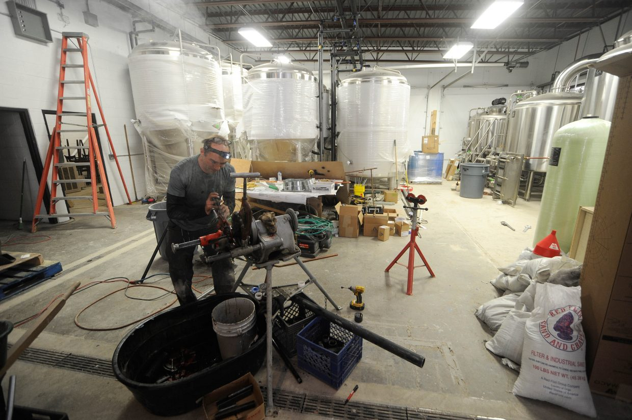 Shad Sills, with Routt Plumbing and Heating, cuts steam pipe Tuesday at Storm Peak Brewing Company's new location at Elk River Road and Lincoln Avenue.