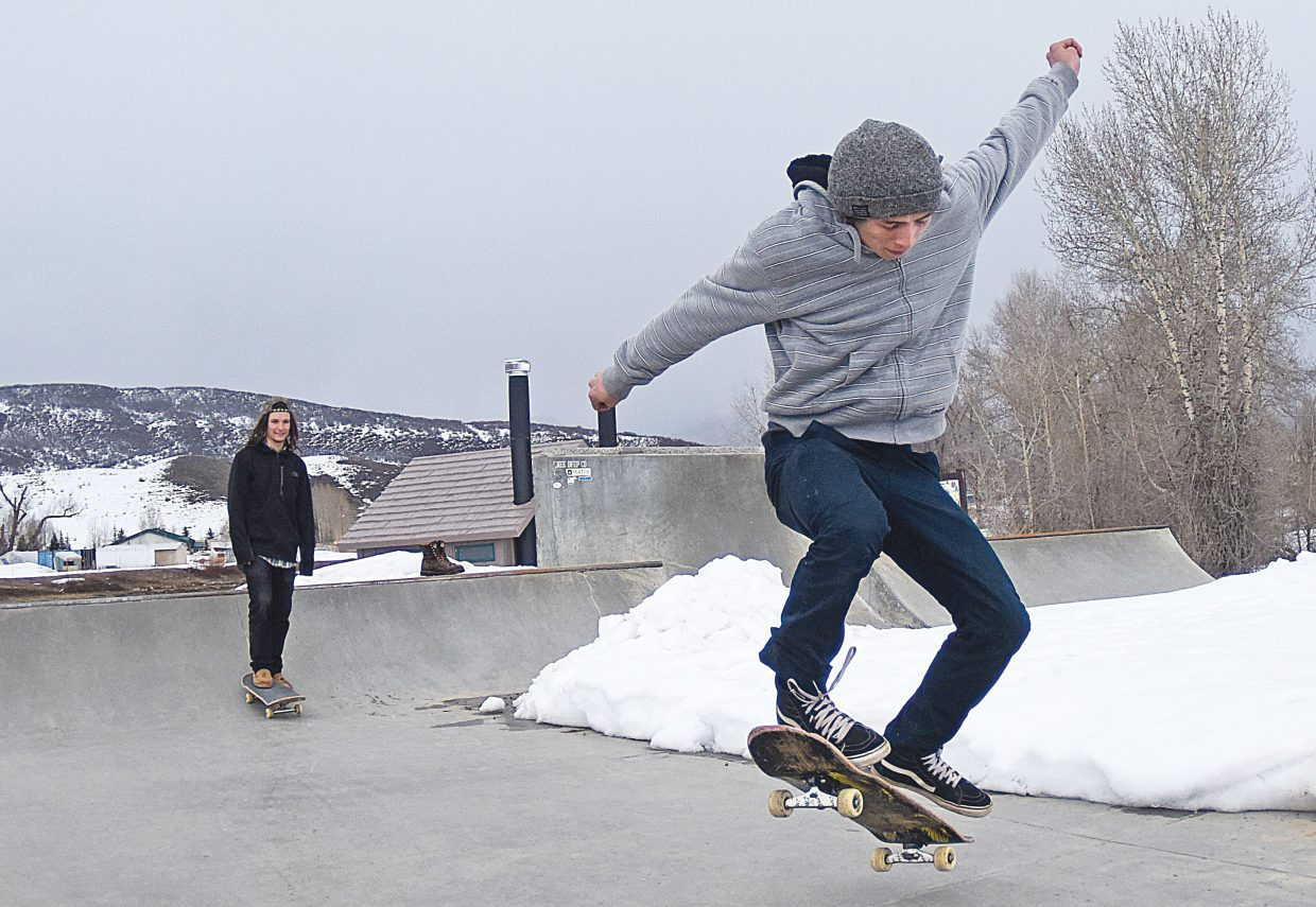 Traegan Strope rides his skateboard at the Bear River Park Tuesday afternoon with a group of friends. Most of the concrete at the park is still covered with snow, but large stretches have been cleared, and local skateboarders are taking advantage.
