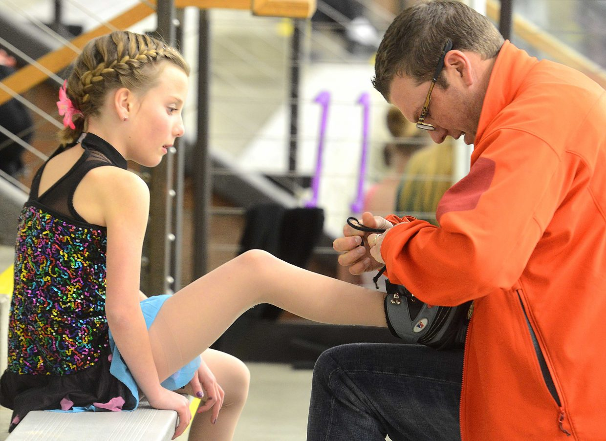 A young skaters gets some help tying her skate Sunday during the Spring Ice Show at Howelsen Ice Arena in Steamboat Springs.