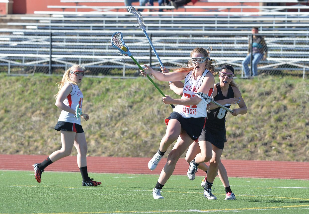 Steamboat Springs Becky Brown gets checked while making a run towards goal during Monday afternoon's girls lacrosse game against Battle Mountain at Gardner Field. The Sailors lost 15-3 to the visiting team in the first home contest of the season for Steamboat. The girls will be back in action at 4 p.m. Friday against Eagle Valley.