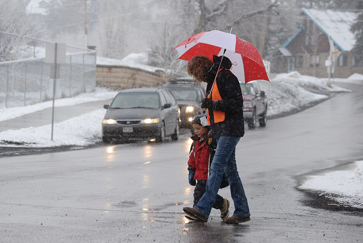 Kindergartner Sawyer Graves gets a helping hand across the street from crossing guard Nancy Hvambsal on Tuesday morning in front of Soda Creek Elementary School. Students and parents woke up to another day of snow as winter attempts to hold on at least for a few more weeks.