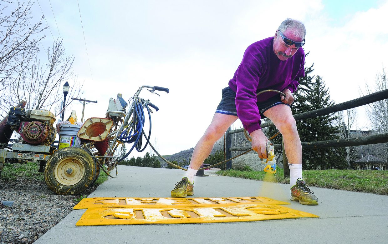 Bill Wernig repaints the warning signs near a crossing on the Yampa River Core Trail Wednesday afternoon. It may feel like spring outside right now, but forecast are calling for cooler temperatures and a chance for snow the next few days.