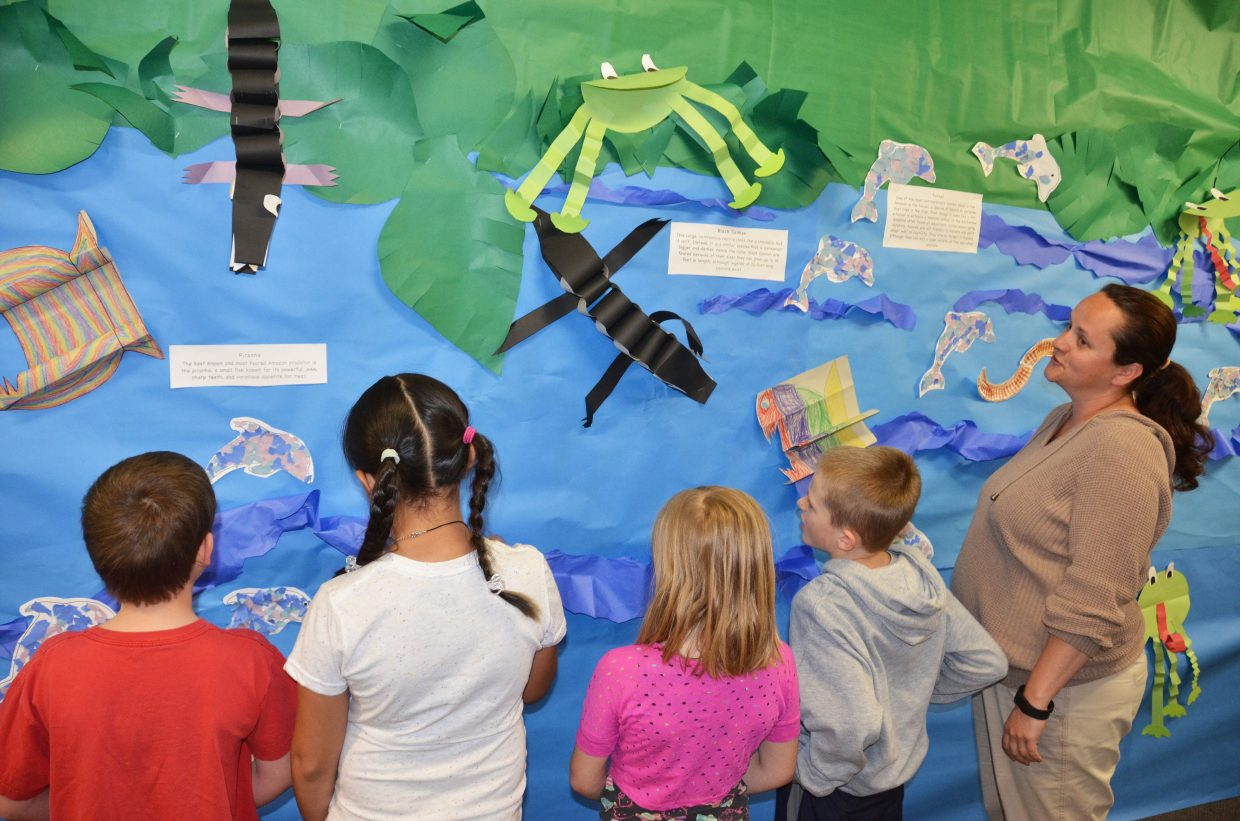 """Second-grade teacher Allison LeWarne talks with students this past week about artwork featuring Brazil at Sandrock Elementary School. The school community celebrates its version of """"International Week"""" every year."""