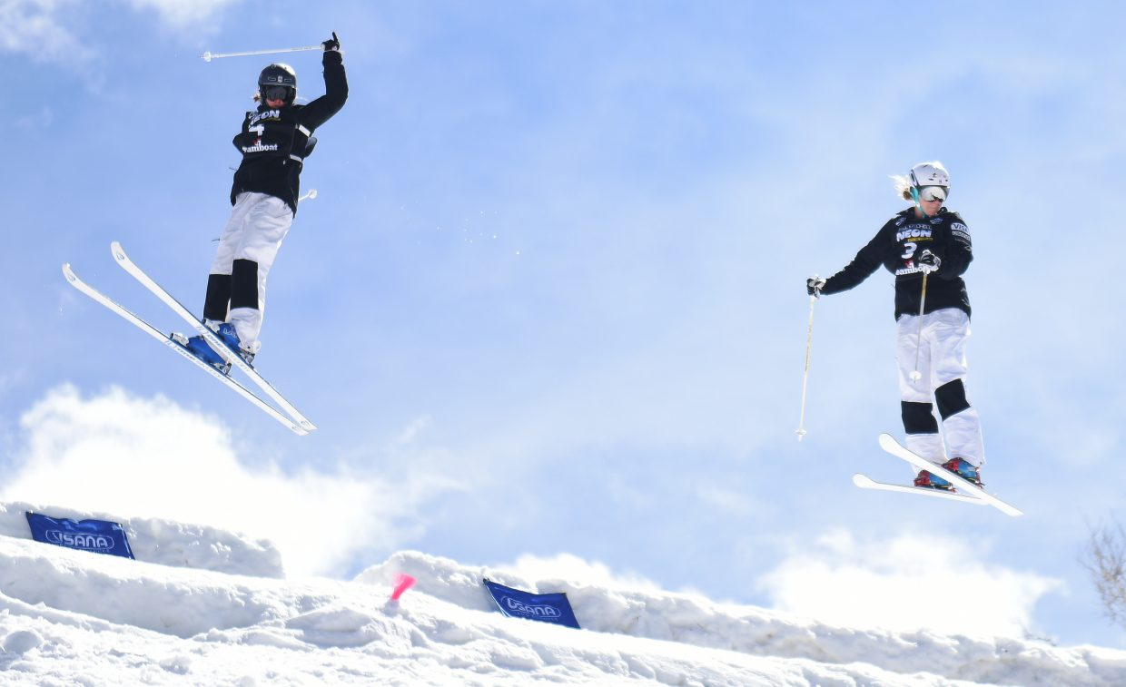 Tess Johnson, left, and KC Oakley both spin through 360s off the top air of Voodoo run Saturday during the dual moguls semifinals at Steamboat Ski Area.