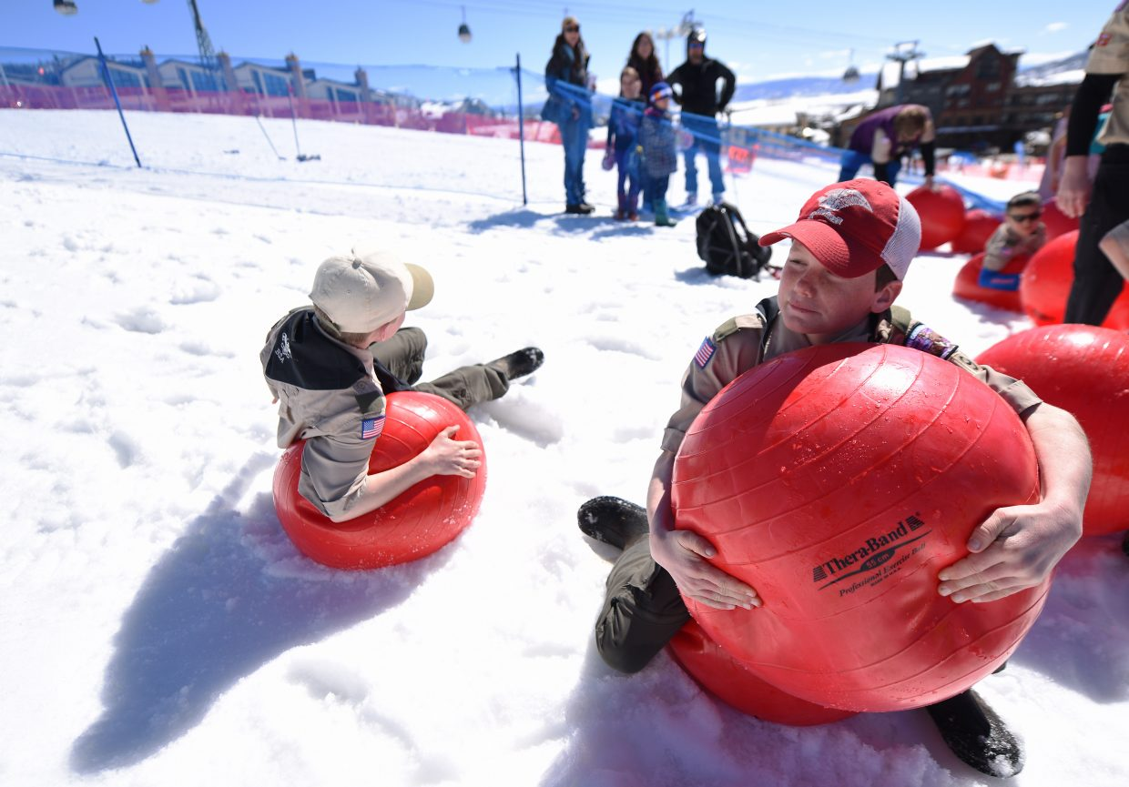 Boy Scout Jason Patrick, right, squeezes to deflate a ball after the second-annual Red Ball Express fundraiser at Steamboat Ski Area.