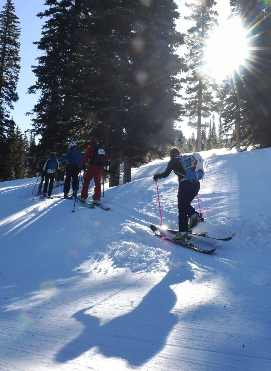 Skiers climb into the trees during Cody's Challenge at Steamboat Ski Area on Saturday.