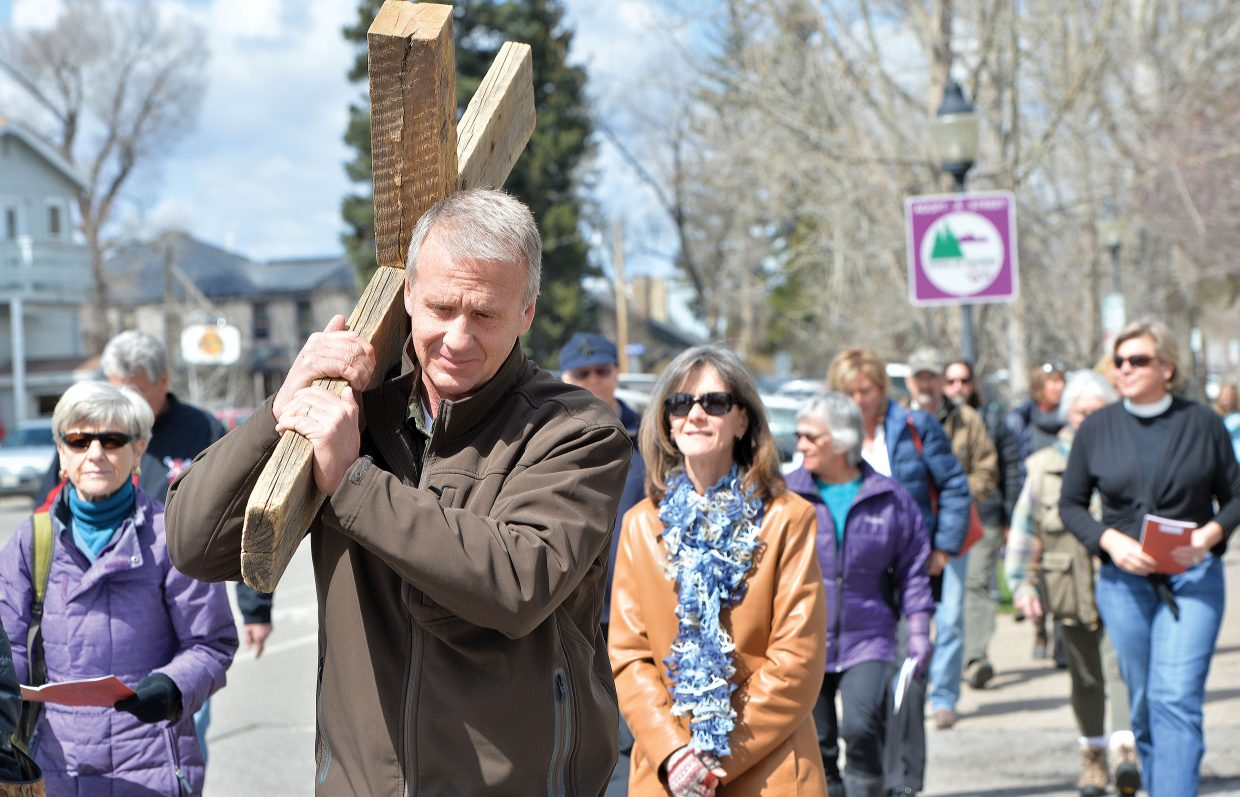 Steamboat Springs resident Tim Jenkins carries the cross down Oak Street Friday afternoon as part of the annual Stations of the Cross. The Stations of the Cross, or the way of the Cross, which is a symbolic pilgrimage highlighting the suffering of Christ as he made his way to Calvary. The group stopped at 14 different locations in downtown Steamboat Springs, stopping at each for a few moments of prayer. The annual remembrance is just one of many events leading up to Easter Sunday.