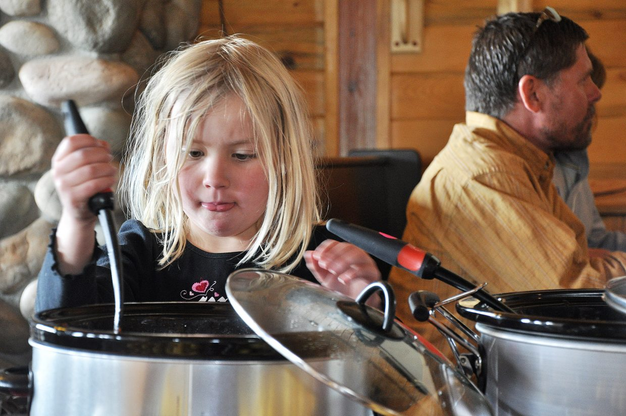 Sydney Lotz reaches in for a ladle of chili at the 10th annual North Routt Chili Cook-Off in 2012. This year's event is from 1 to 5 p.m. Sunday.