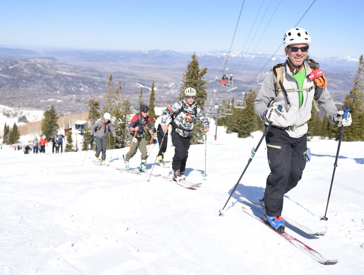 DanGilchrist climbs beneath the Storm Peak Express chairlift at Steamboat Springs on Saturday during Cody's Challenge.