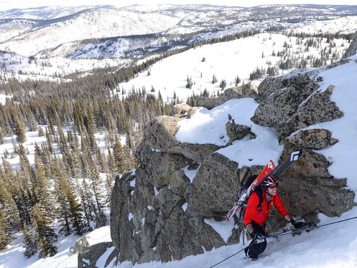 Andrew Miller hikes under the Rancid Tuna rocks Saturday at Steamboat Ski Area during Cody's Challenge.
