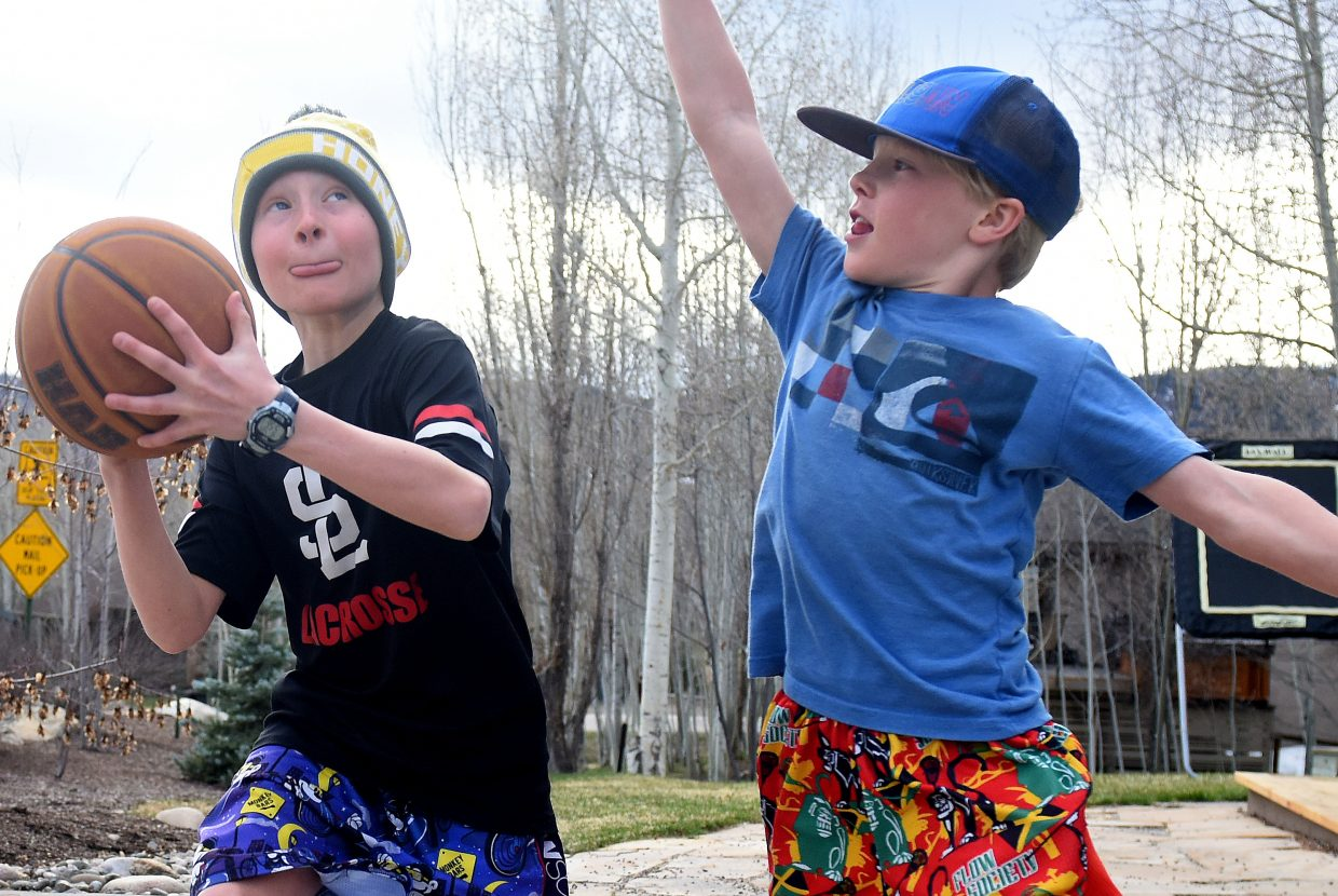 Block party: Mac Redfern, 11, looks to get a shot past his younger brother, George Redfern, 9, on Wednesday. The brothers spent a cool but dry early-April afternoon playing hoops in their Steamboat Springs driveway.