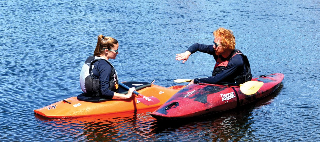 Roddy Beall teaches Jordan Edwards some kayaking skills in Fetchers Pond on Monday afternoon.