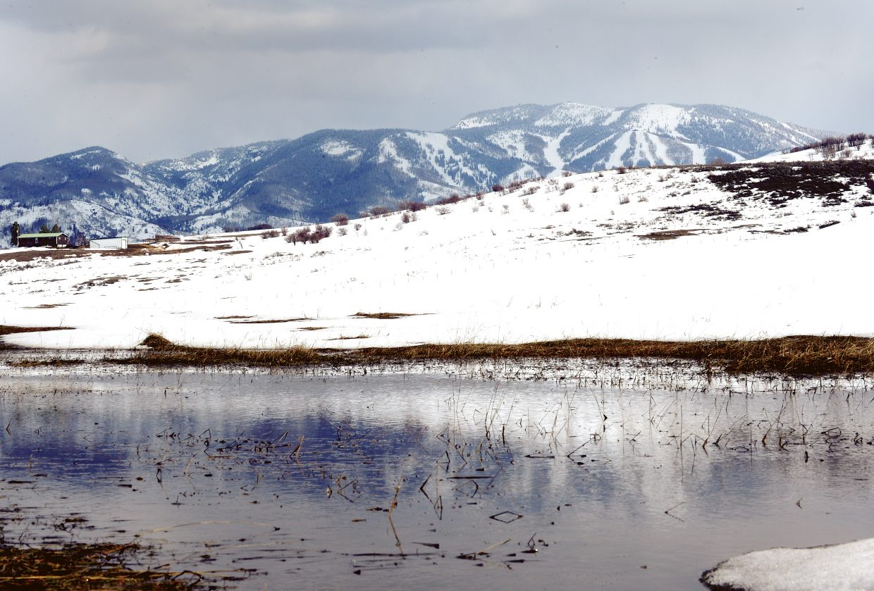 The ski slopes of Steamboat Ski Area are reflected in a small pond formed in a pasture west of Steamboat Springs.