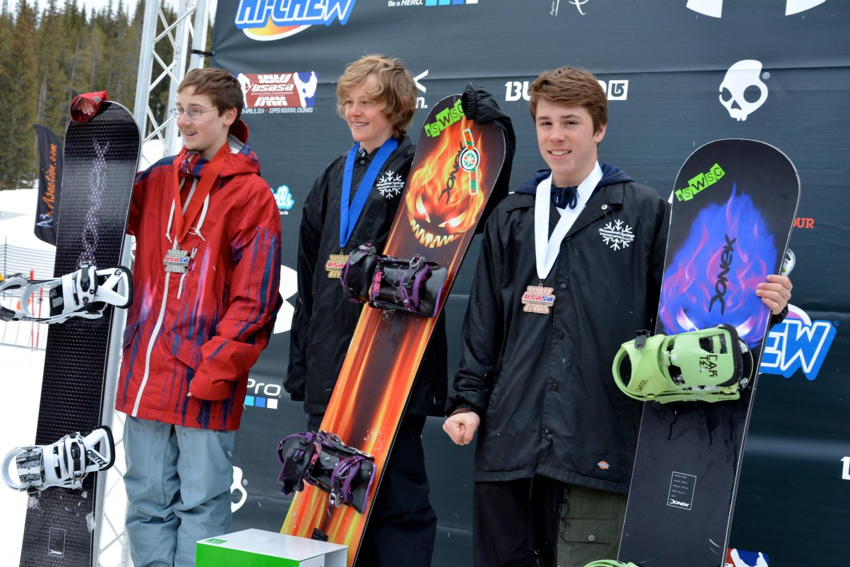 Steamboat Springs Winter Sports Club snowboarders Ryan Merritt, right and in third, and Cody Winters, center and in first, stand on the podium after their big finishes in the snowboard cross event at the USASA National Championships in Copper Mountain.