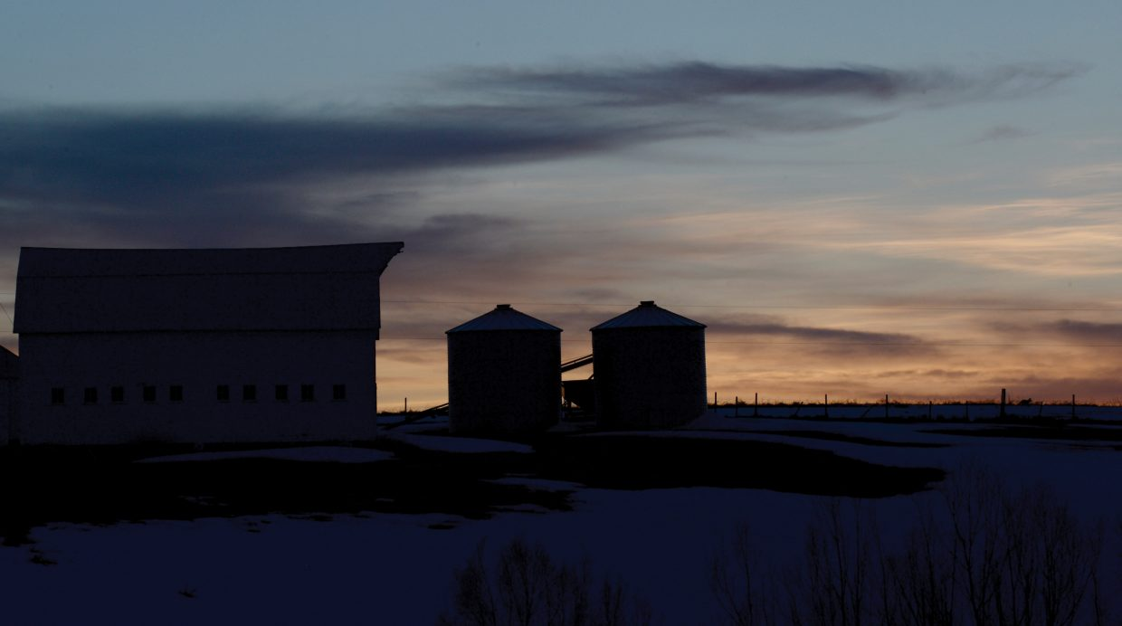 The sun sets behind an old barn west of Steamboat Sprngs on Tuesday evening.