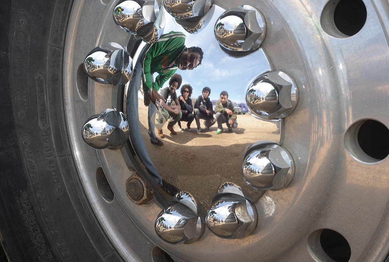 The Groovetrotters, shown reflected in the wheel of the group's tour bus, travel across the country bringing a mix of jazz, funk, reggae and rock all melded into a controlled jam session. This is a family group with dad Marcel Groovetrotter leading the way on guitar and his sons Pierre, Jerome, BJ and Claude filling out the group.