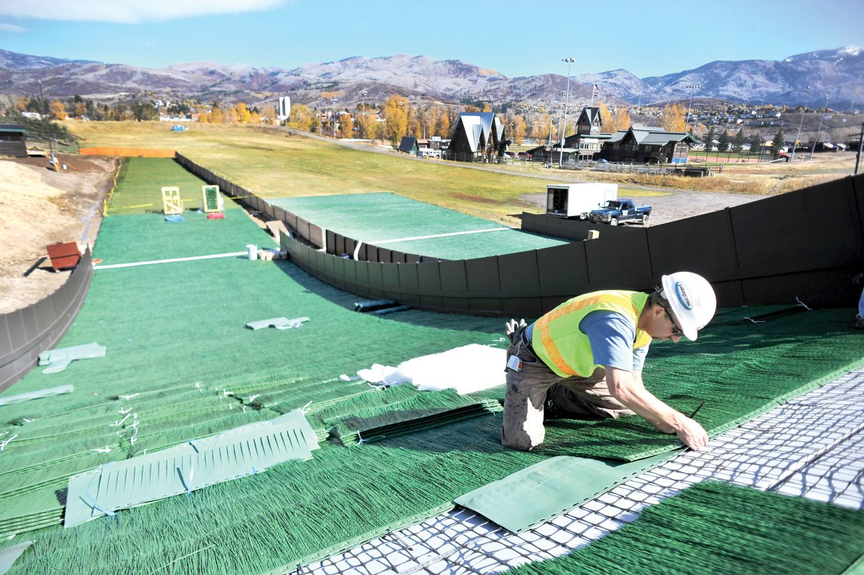 Steamboat Springs Winter Sports Club Nordic coach Todd Wilson attaches sections of plastic to the new year-round ski jumps at Howelsen Hill in 2012. The city's current list of parked capital projects totals $128 million and includes such projects as the rehomologation of jumps on Howelsen Hill and major highway upgrades.