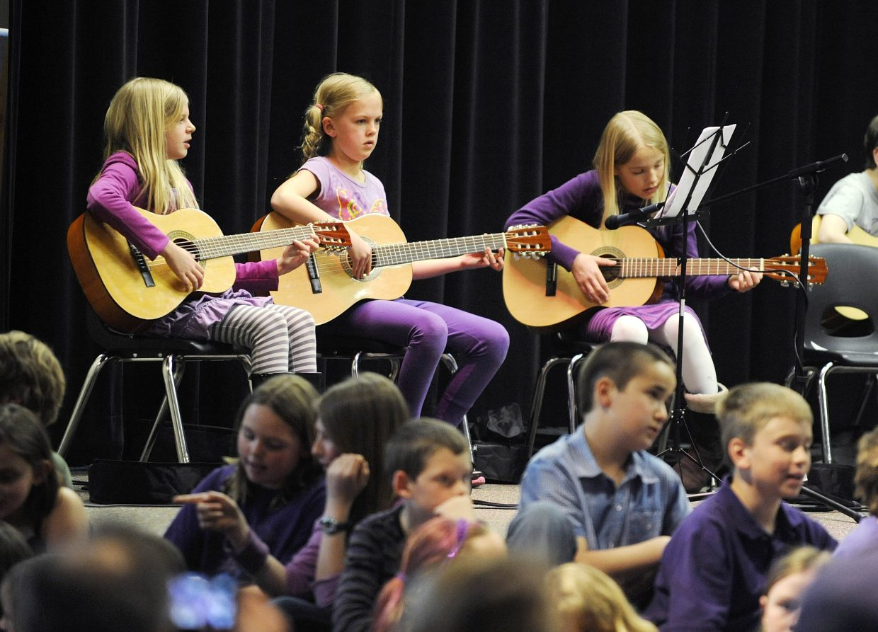 Soda Creek Elementary School fourth-graders, from left, Madeline Huge, Caroline McLaughlin and Grace Schoen perform Thursday during a concert at the school.
