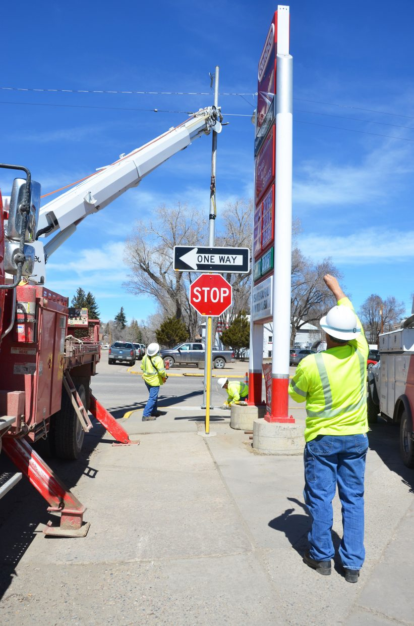Groundman Saul Hernandez, left, Lineman Levi Schnackenberg and Line Crew Foreman Todd Greenwood work on the corner of Victory Land and School Street to replace a light pole that had been damaged during the winter.