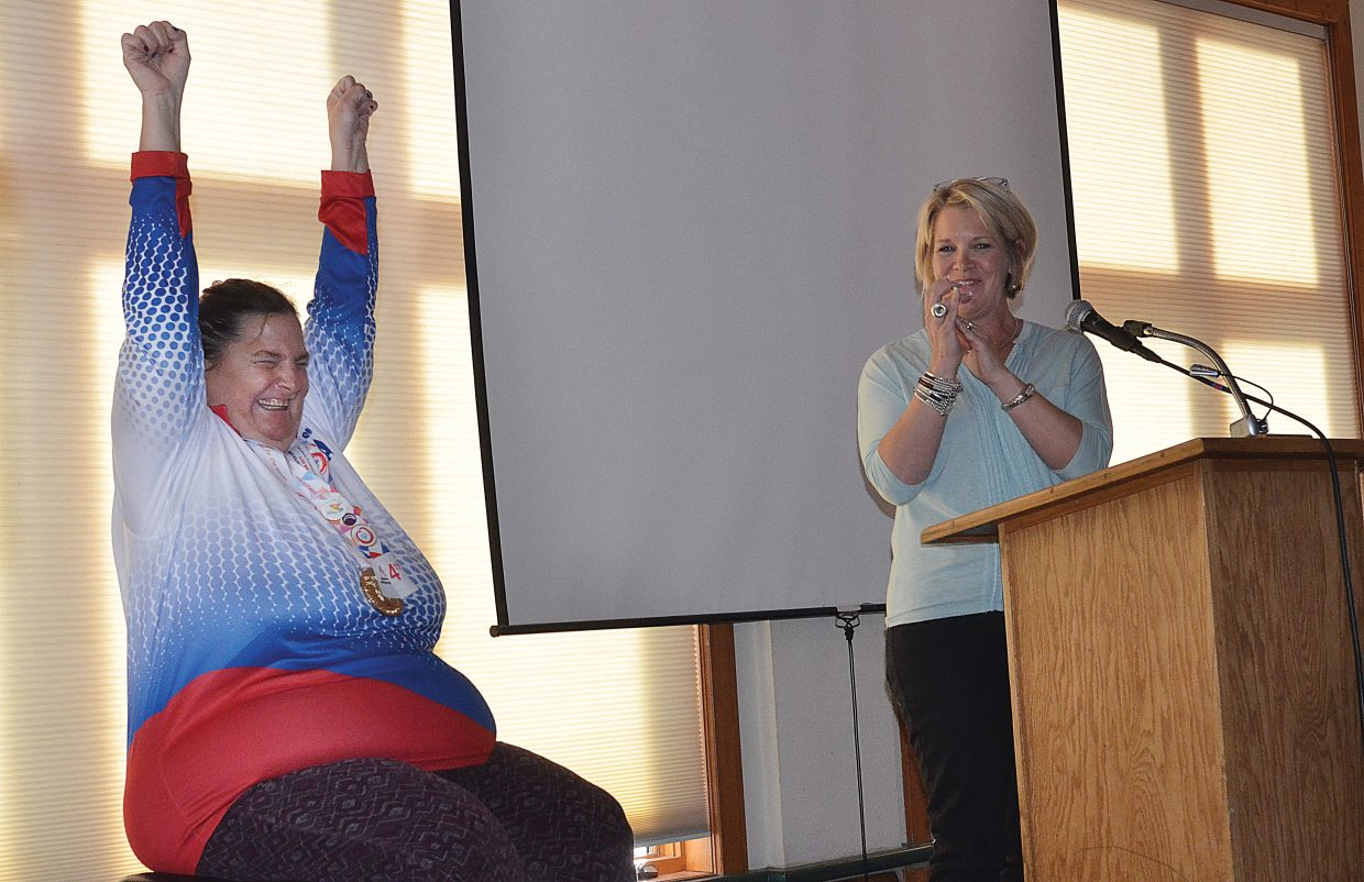 Sue White holds her hands over her head celebrating her gold medal showing in the giant slalom at the 2017 Special Olympic World Winter Games, which took place last month in Austria during a speech by Julie Taulman, executive director of STARS.