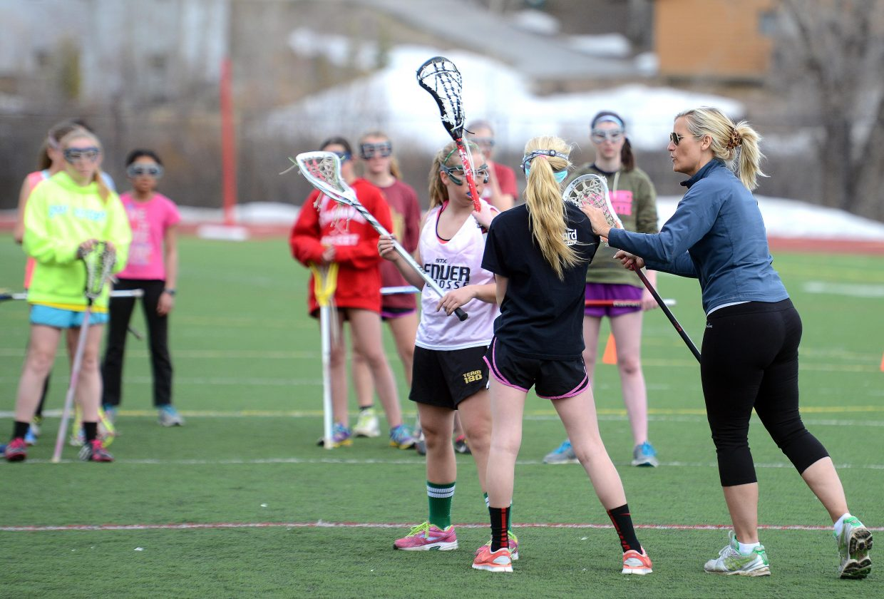 Deb Kuzemchak offers coaching to a pair of middle school girls lacrosse players on Saturday during a practice at Steamboat Springs High School. Kuzemchak played the game in college and her eighth-grade daughter, Delaney Pratt, has been playing lacrosse for nine years. Kuzemchak hopes to help get a girls lacrosse traveling team together for tournaments this summer, then to sustain the program to allow it to grow in to a feeder program for the girls high school team.
