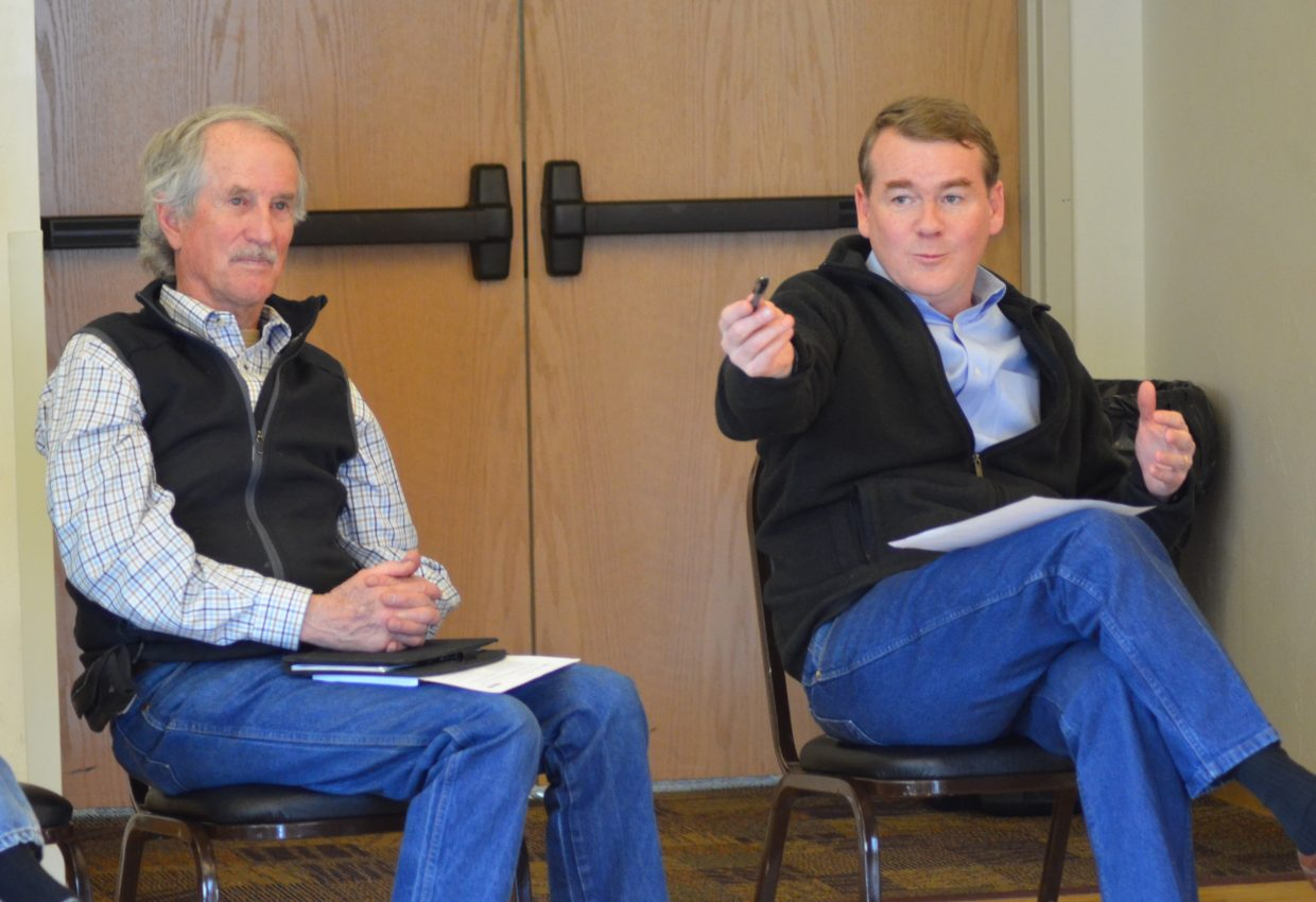 Colorado Sen. Michael Bennet, right, speaks to farmers and agriculture advocates Tuesday while rancher Jay Fetcher listens.