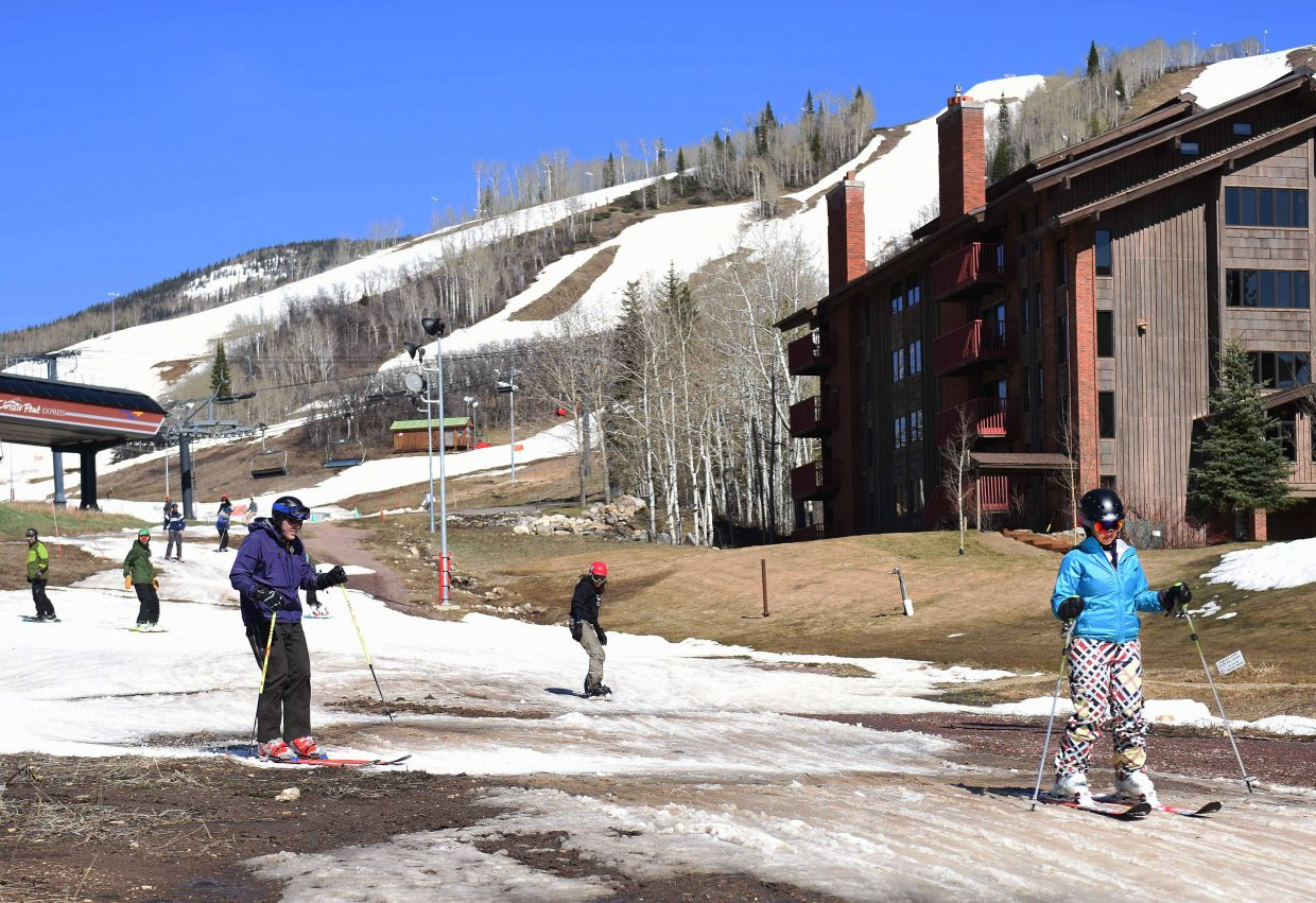 Skiers navigate their way through patches of mud on Sunday as they head down from their final runs of the 2014-2015 skiing season at Steamboat Ski Area. Nearly a month of 60-degree weather took a severe toll on the trails on the lower portions of Mount Werner, but crews managed to keep access open to the base area through closing day despite that weather, and the mountain's upper slopes were in much better condition, offering skiers plenty of opportunity for one last glorious day of carving.