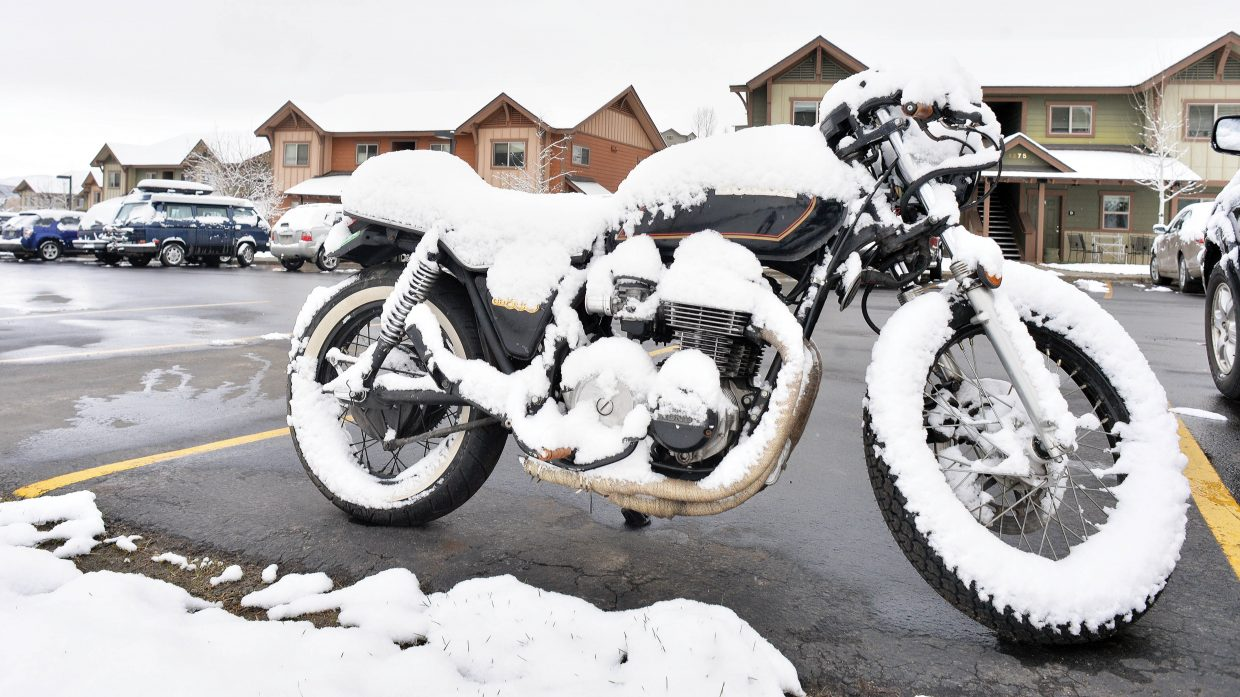 A thin layer of snow covers a motorcycle in a parking lot off of Hilltop Parkway in Steamboat Springs after a snowstorm moved through the area late in the week.