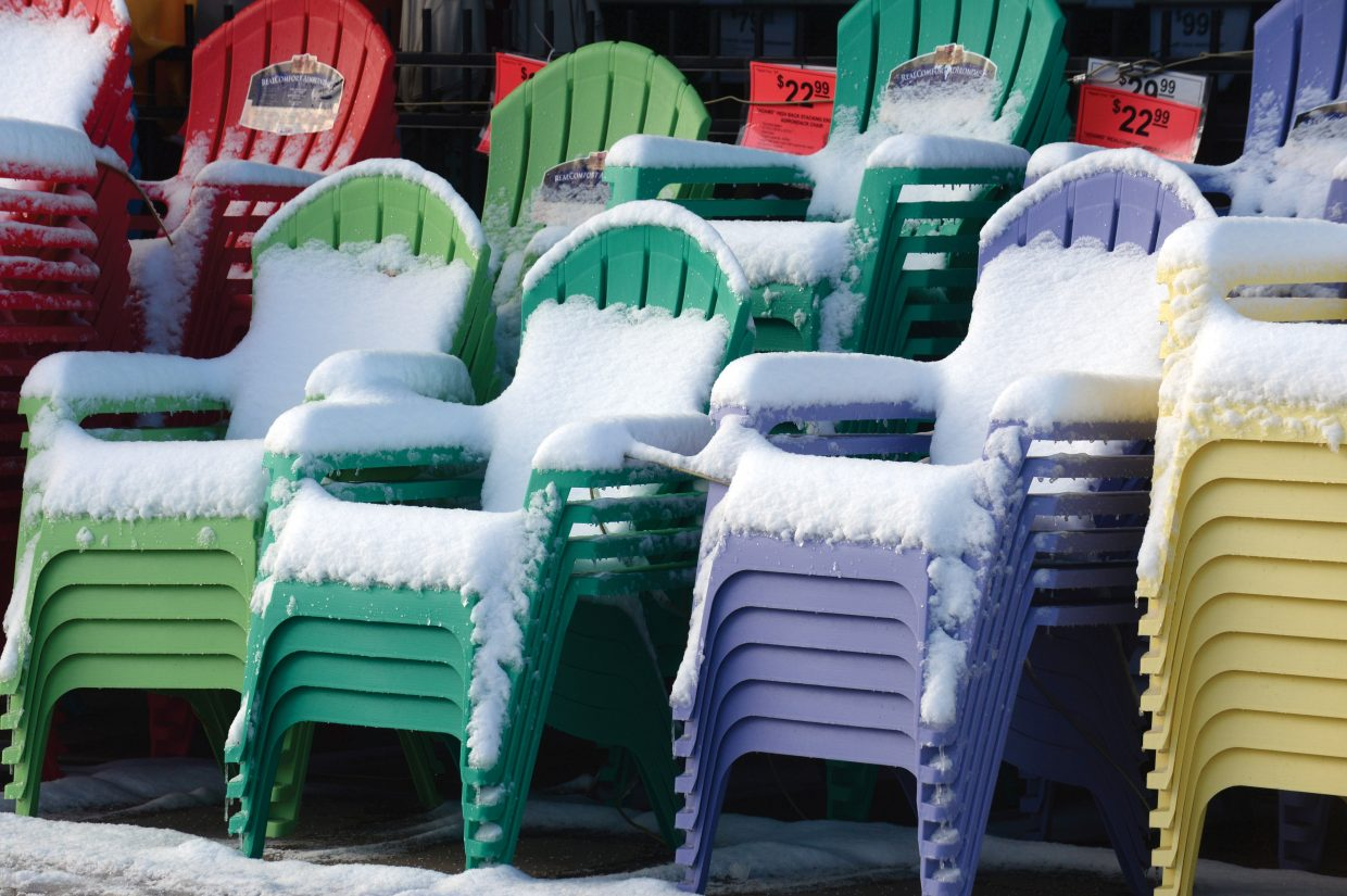 Snow covers brightly colored lawn chairs outside Ace Hardware in Steamboat Springs. The calendar says it's spring, but that doesn't mean the area has escaped winter's icy grip.