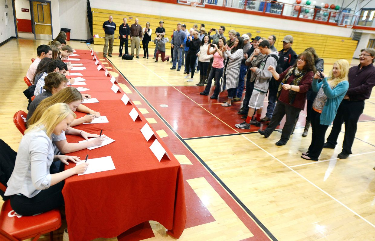 Parents and coaches snap photos and cheer Wednesday as about a dozen Steamboat Springs High School athletes sign letters of intent to play sports in college.