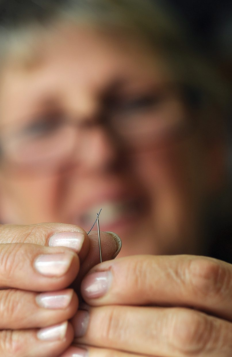 Sew What owner Maggie Bentz threads a needle at the downtown Steamboat Springs shop.