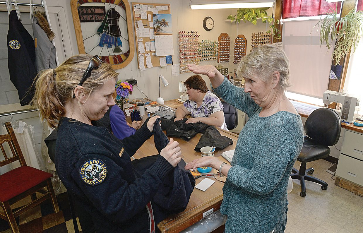 Kelly Halpin, who works for Colorado Parks and Wildlife, talks with Maggie Betz about alterations to her uniform at Sew What. Sew What employee Trish Tomme is hard at work in the background.