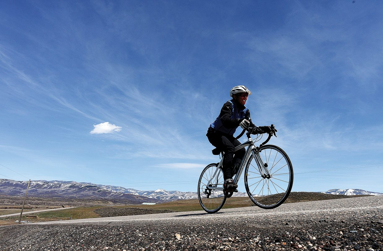 Michelle Isaeff makes her way up a hill while riding her bike along Twentymile Road on Thursday near Steamboat Springs. Isaeff was treated to a wonderful spring day, but the snow-covered slopes of Steamboat Ski Area in the background remind us all that winter isn't too far behind us.