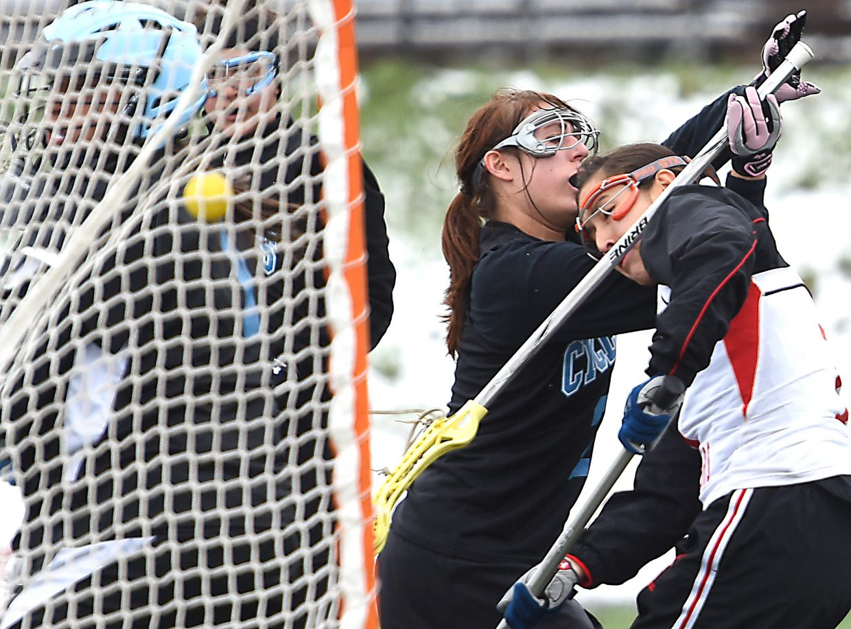 Emi Costantini gets all wrapped up with a Pueblo West defender after she tossed the ball into the back of a net for a goal late in Saturday's game.