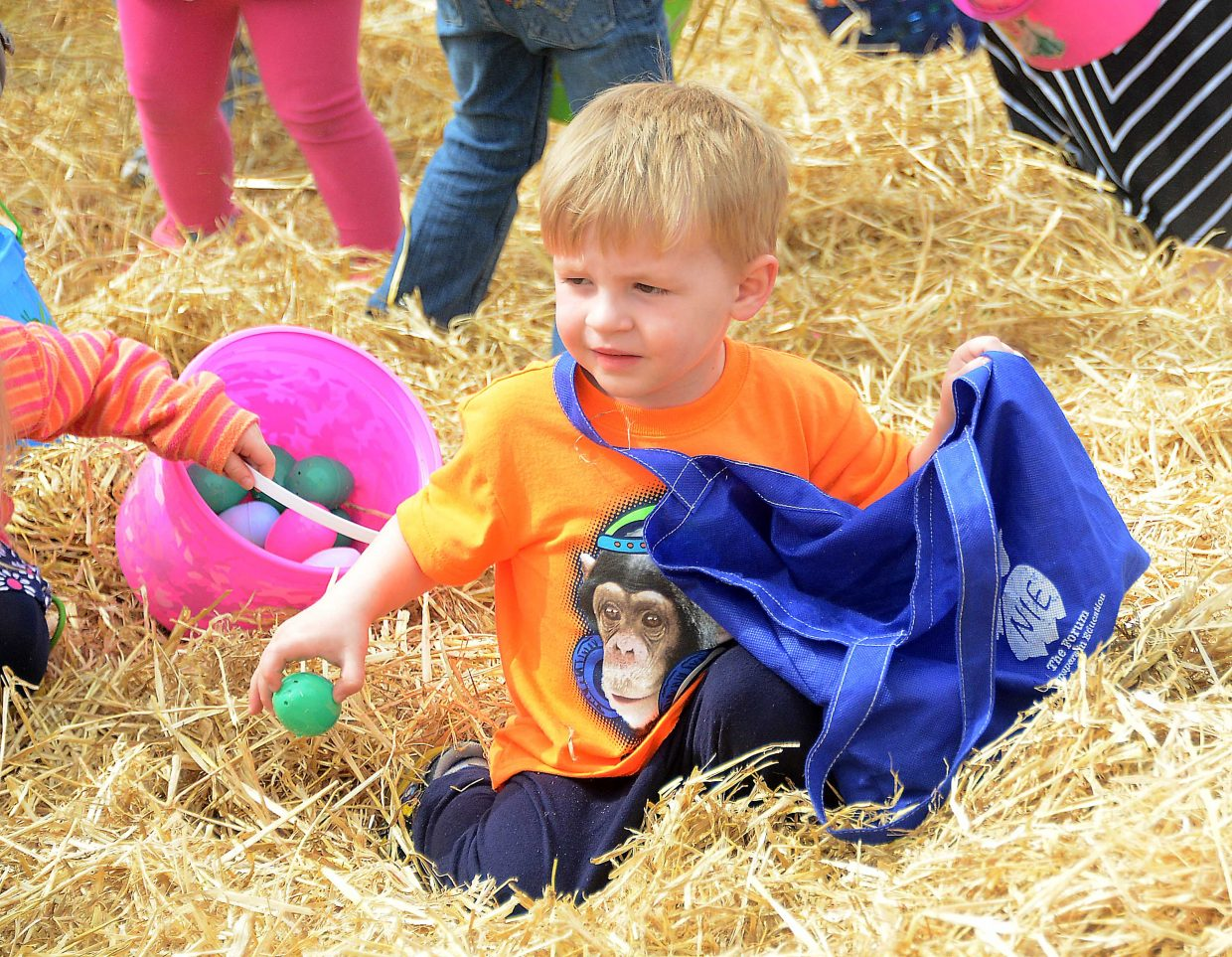 Anders Ornberg, 2, pulls in an egg Saturday.