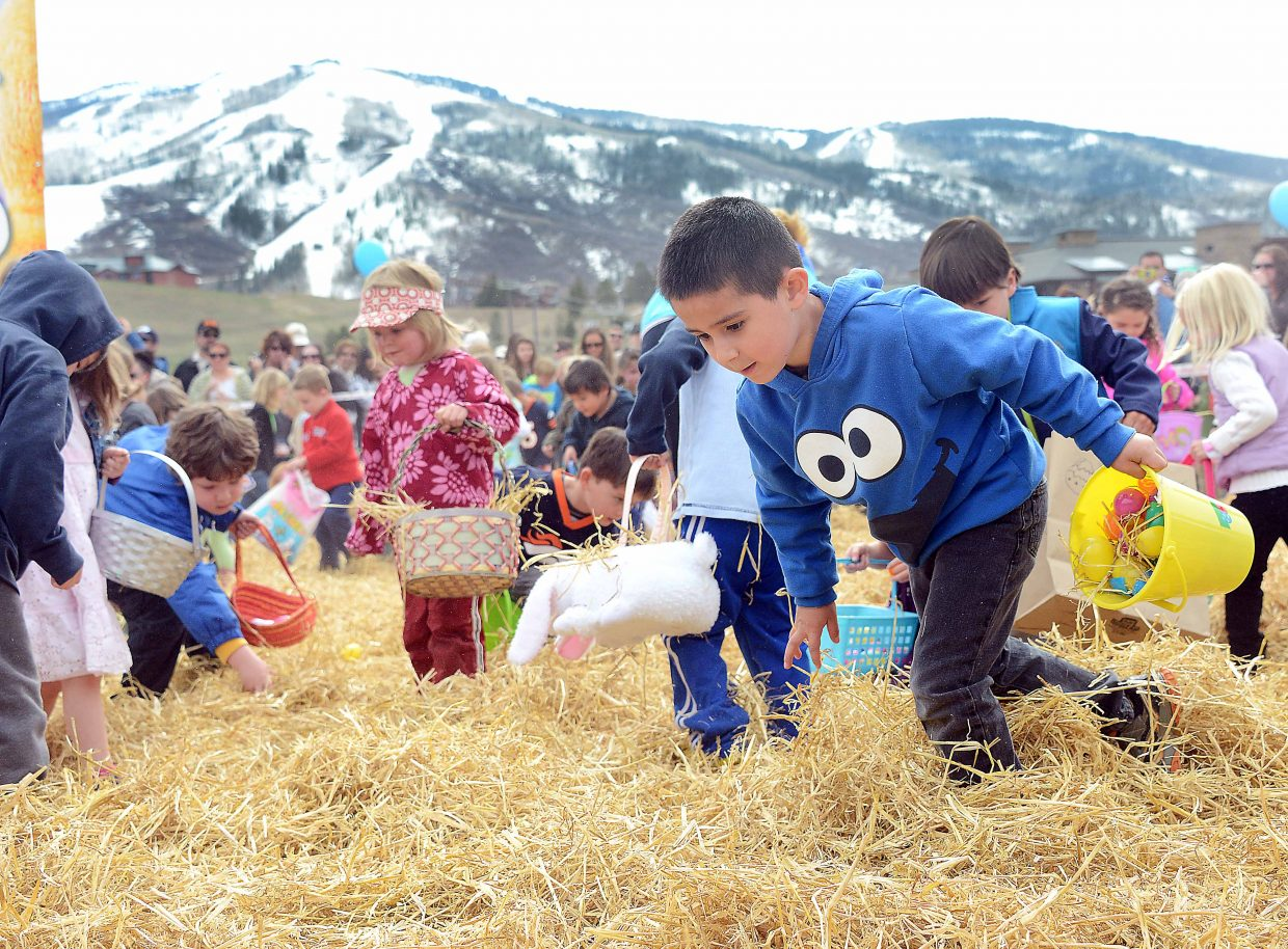 David Morales, 5, combs through the straw looking for eggs during the annual Easter Eggstravaganza at the Meadows parking lot in Steamboat Springs. Morales was one of hundreds of children who showed up and scored big, each pulling in their share of thousands of hidden eggs.